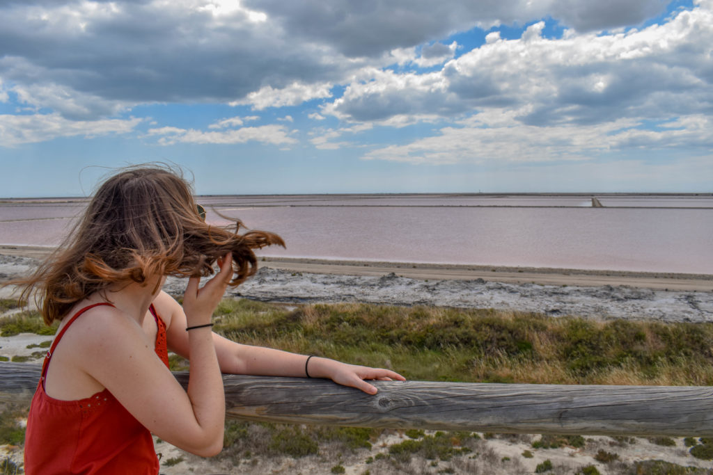 Une fille fait voler ses cheveux en contemplant les salins