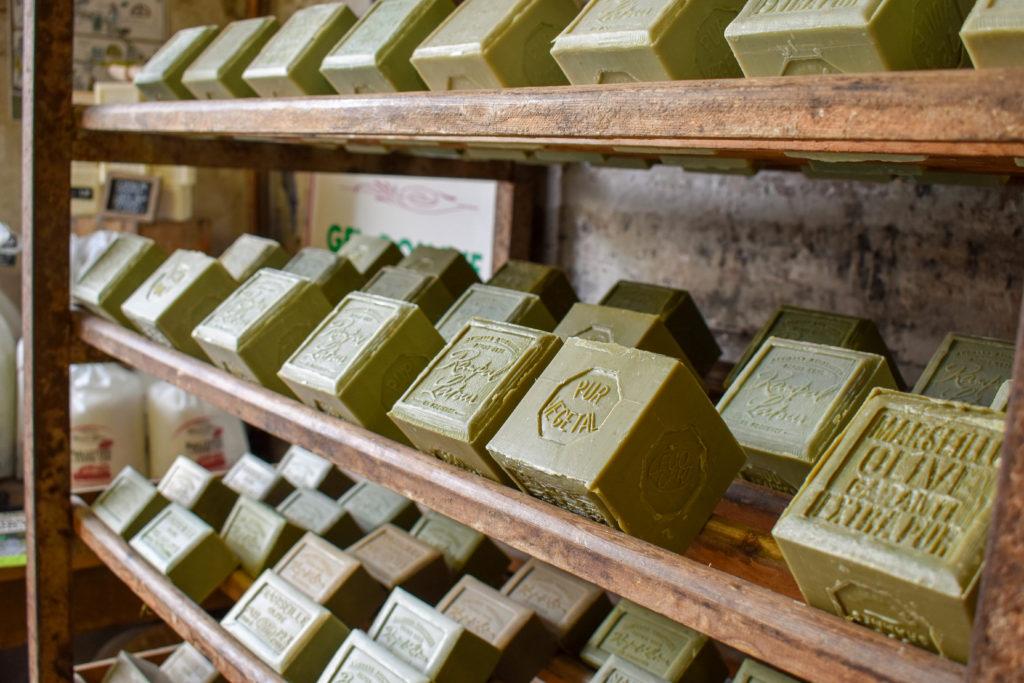 savon de marseille vert exposé sur des étagères en bois