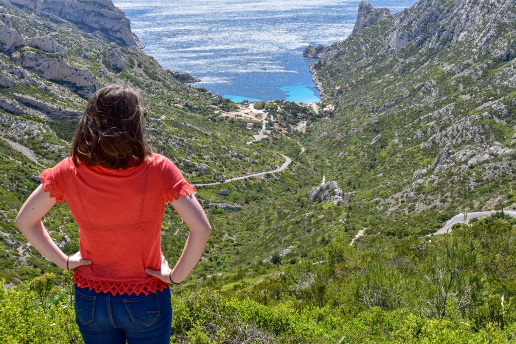 Une fille de dos devant une Route sinueuse qui va jusqu'au creux d'une calanque entourée de falaise
