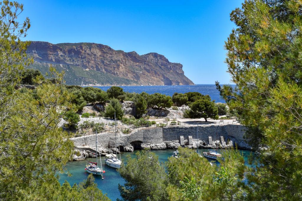 calanque entourée de falaise et quelques bateaux dans un petit port