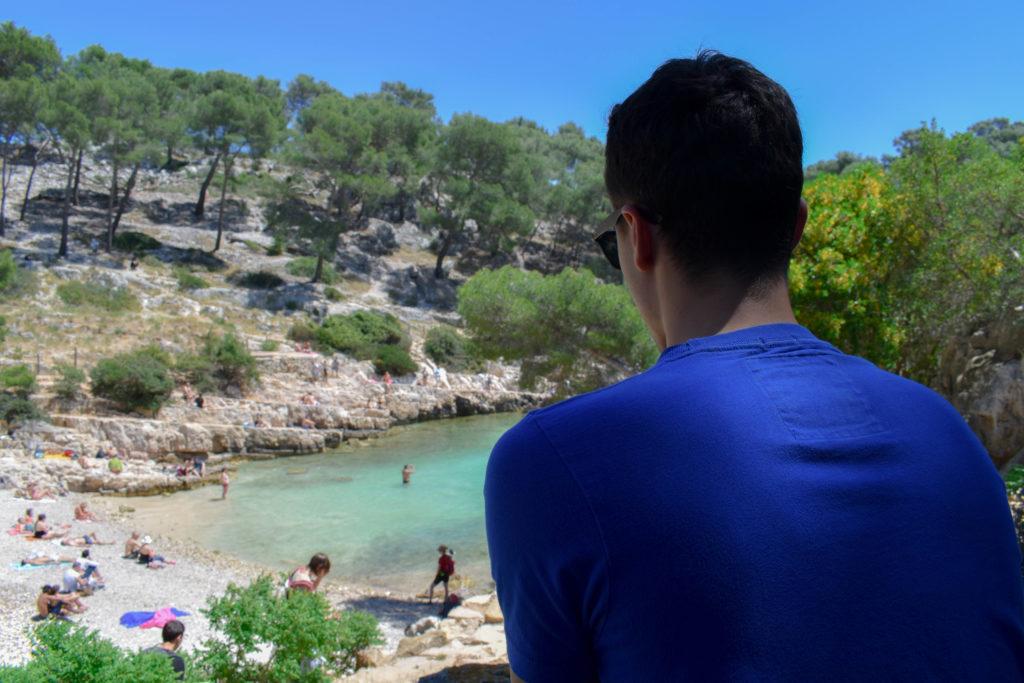 garçon de dos devant eau bleue turquoise des calanques entourée de pinède