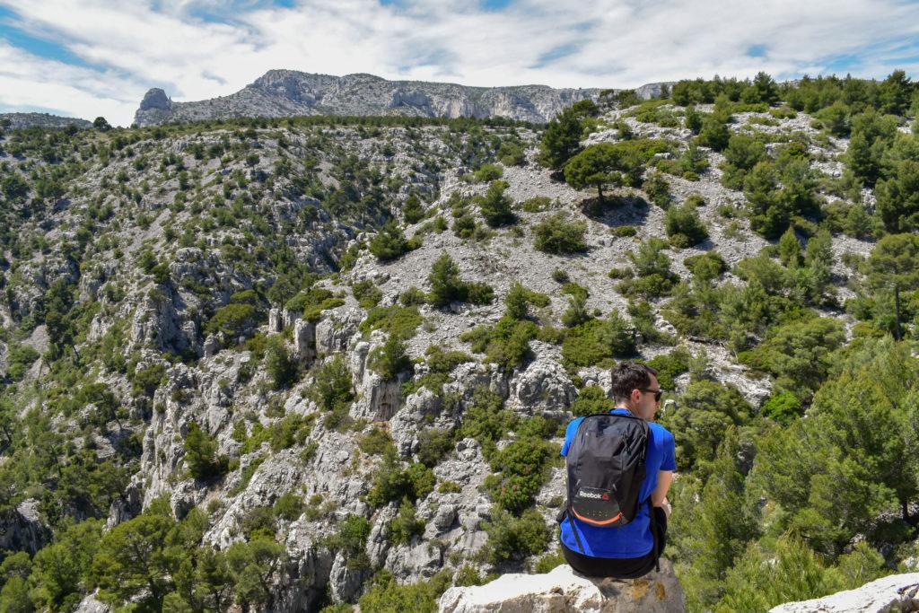 garçon de dos assis dans Paysage rocailleux dans les calanques
