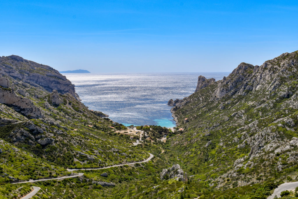 Route sinueuse qui va jusqu'au creux d'une calanque entourée de falaise